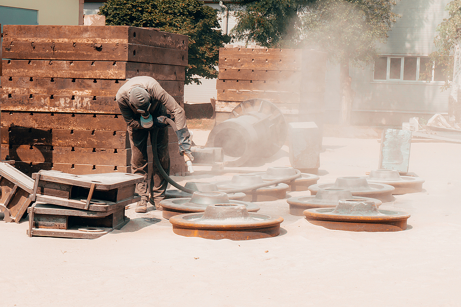 Worker while doing a mobile sand blasting