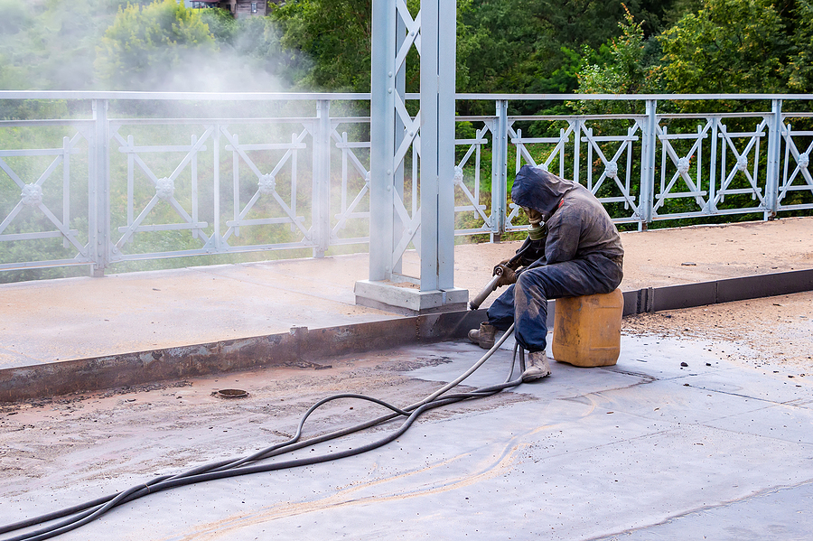Worker with protective mask doing a mobile sand blasting